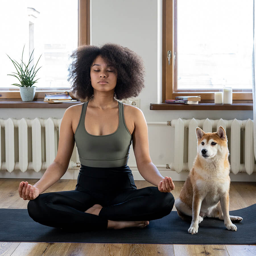 woman sitting in a meditative yoga position next to her dog